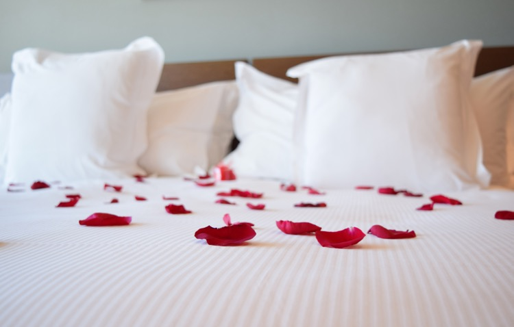 a bed with white bedding and red rose petals