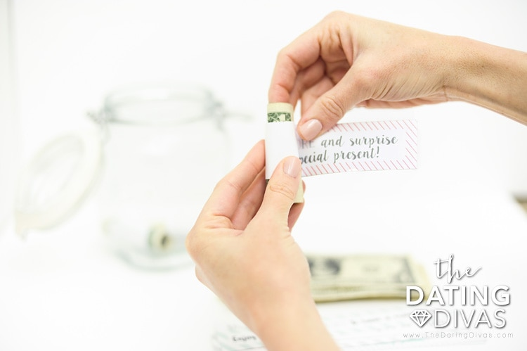 2 hands wrapping paper around dollar bill for date night jar