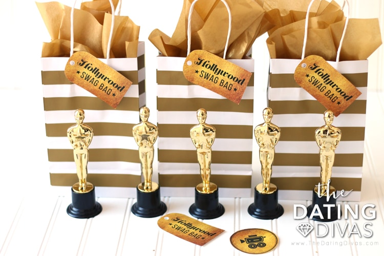 Meet my Oscars Party Swag Bags. I filled the swag bags with my printable Oscars Scorecards, Sequin Star Barrettes, Tuxedo Confetti Poppers, Gold Notebooks from Target, and Mini Champagne Bottles from Target with pretty ribbon and striped straws.