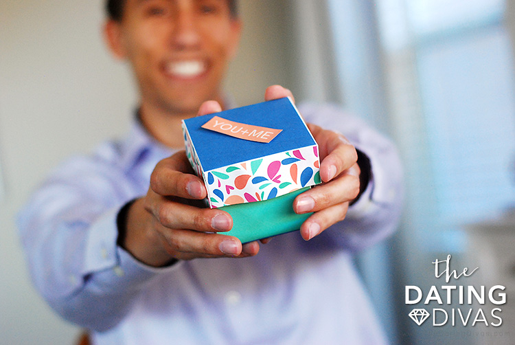 Hands holding a DIY explosion box filled with romantic ideas | The Dating Divas