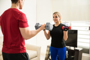 A husband and wife doing bicep curls at home | The Dating Divas