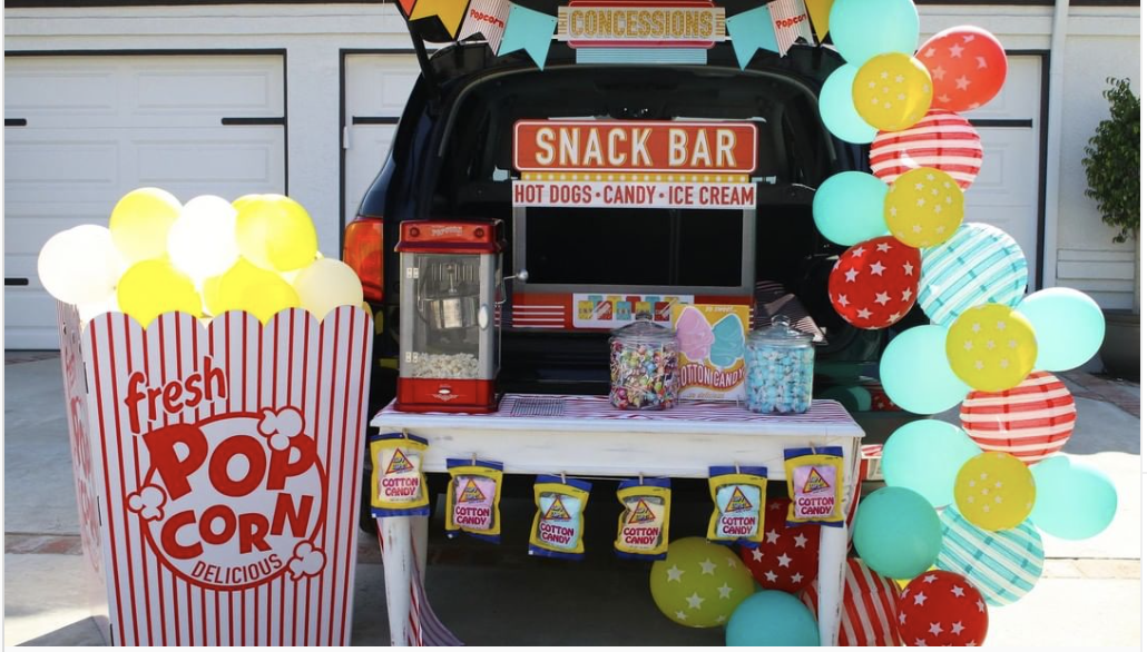 A trunk decorated with a snack bar and popcorn maker to create a concession stand theme for a trunk or treat event | The Dating Divas