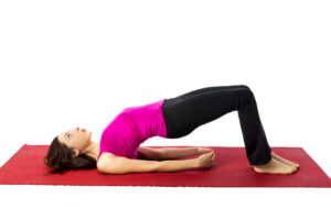 Wife practicing the lying gluteal bridge on a yoga mat for Sexercise date | The Dating Divas