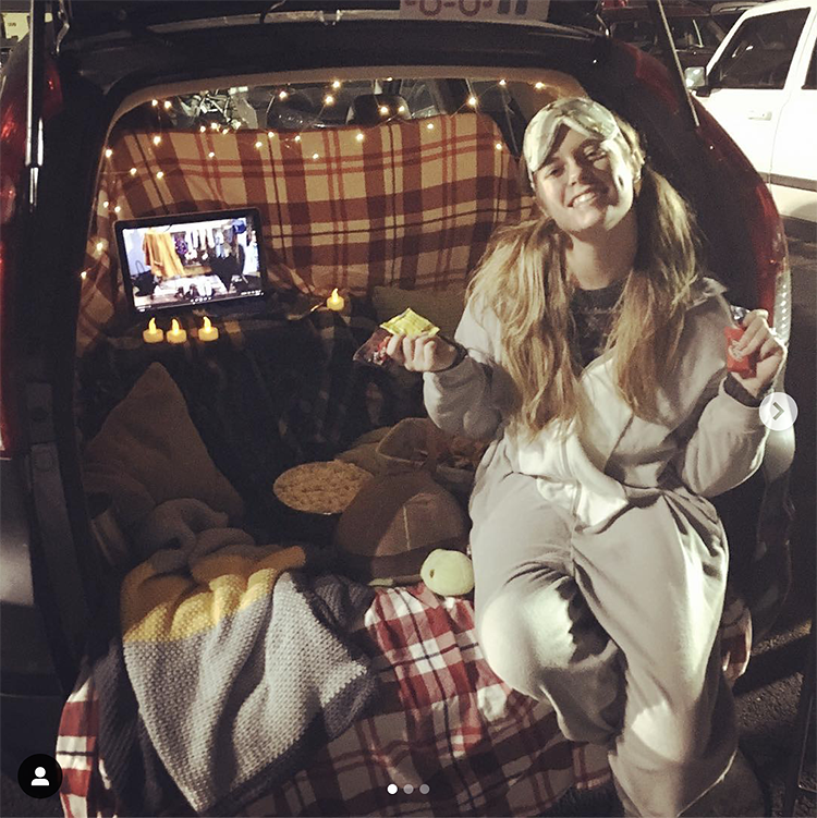 A trunk decorated with pajama party items including candles, a movie screen and junk food. A person is dressed in pajamas and a face mask. This is an easy trunk or treat Halloween decorating idea.