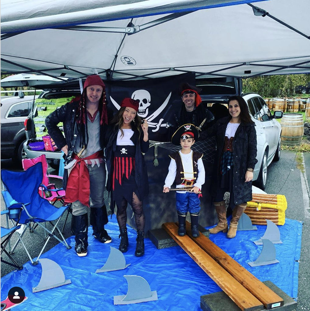 A trunk decorated a pirate ship with a blue tarp laid out in front to create a sea scene (including with sharks!) - a fun trunk or treat decorating idea | The Dating Divas
