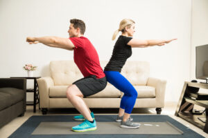 A man and woman doing squats back-to-back at home | The Dating Divas
