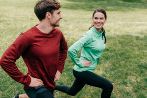 A man and women doing tandem stationary lunges for sex workout date | The Dating Divas