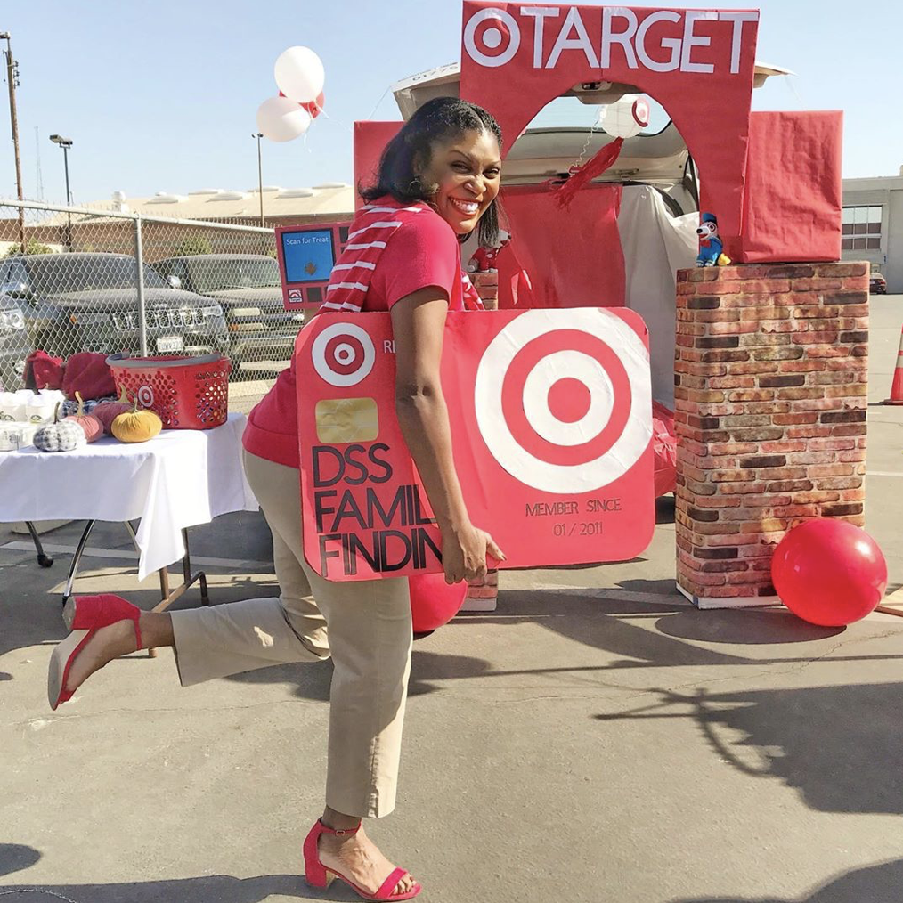 A car trunk decorated as a Target store. A person is dressed as a Target employee carrying an oversized Target Red Card. A fun idea for Trunk or Treat | The Dating Divas
