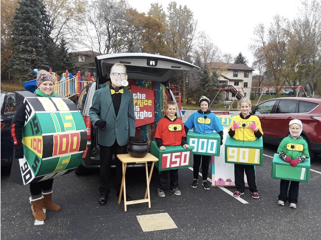 A family dressed as characters from the tv show The Price is Right standing in front of a decorated trunk for a trunk or treat event | The Dating Divas