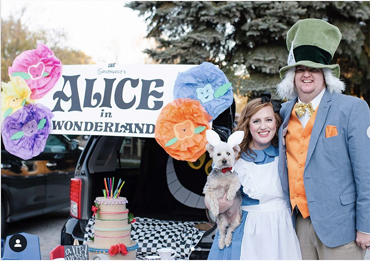 Trunk decorated with an Alice in Wonderland theme including a very unbirthday cake and a large Cheshire cat - a great trunk or treat idea | The Dating Divas