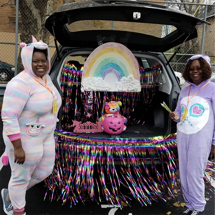 Trunk decorated with a care bear theme including a large rainbow and coordinating Care Bear costumes. This is a great trunk or treat idea | The Dating Divas