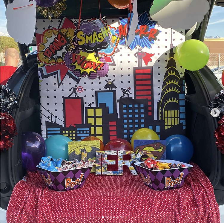 A trunk decorated with a classic building scene from a superhero comic book. There are blue, red and yellow windows and signs. This is such a fun trunk or treat idea for Halloween. | The Dating Divas