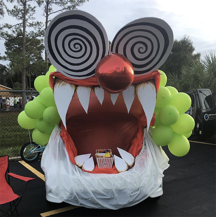 A trunk decorated as a large mouth of a crazy circus clown. The trunk is the mouth of the monster. This is a very popular and easy trunk or treat idea. | The Dating Divas