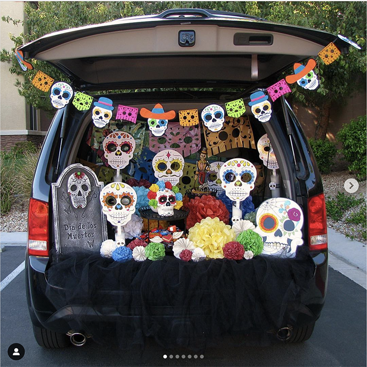 Trunk decorated with a day of the dead (dia de los muertos) theme. It is a colorful display with skeletons, flowers and papel picado. A fun trunk or treat idea. | The Dating Divas