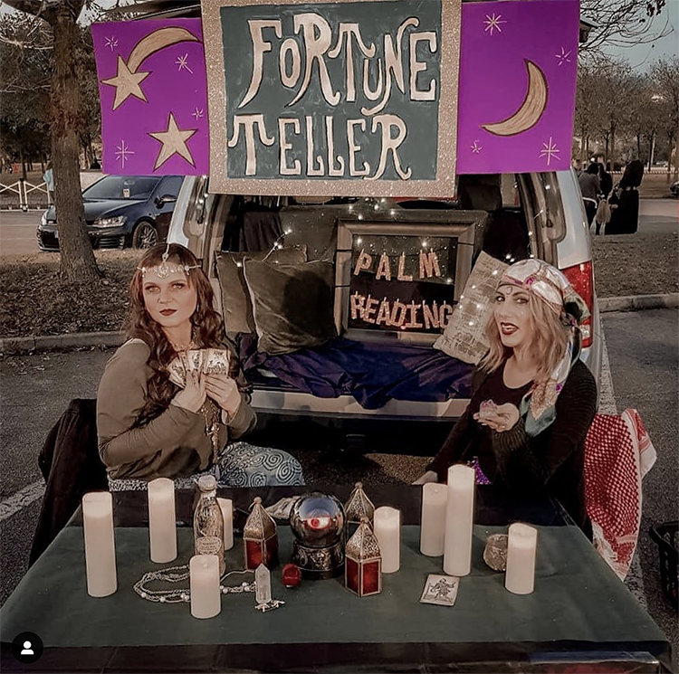 A trunk decorated with candles, moons and stars. There are two women dressed as fortune tellers. There is a table. The idea for this trunk is to not only get a candy but also to get your fortune told. A fun interactive trunk or treat idea. | The Dating Divas