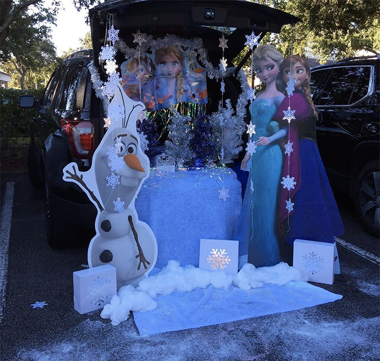 Trunk decorated with a theme for Disney's frozen. It includes snowflakes and stand up cardboard cut outs of characters from the show. This is a great trunk or treat idea | The Dating Divas