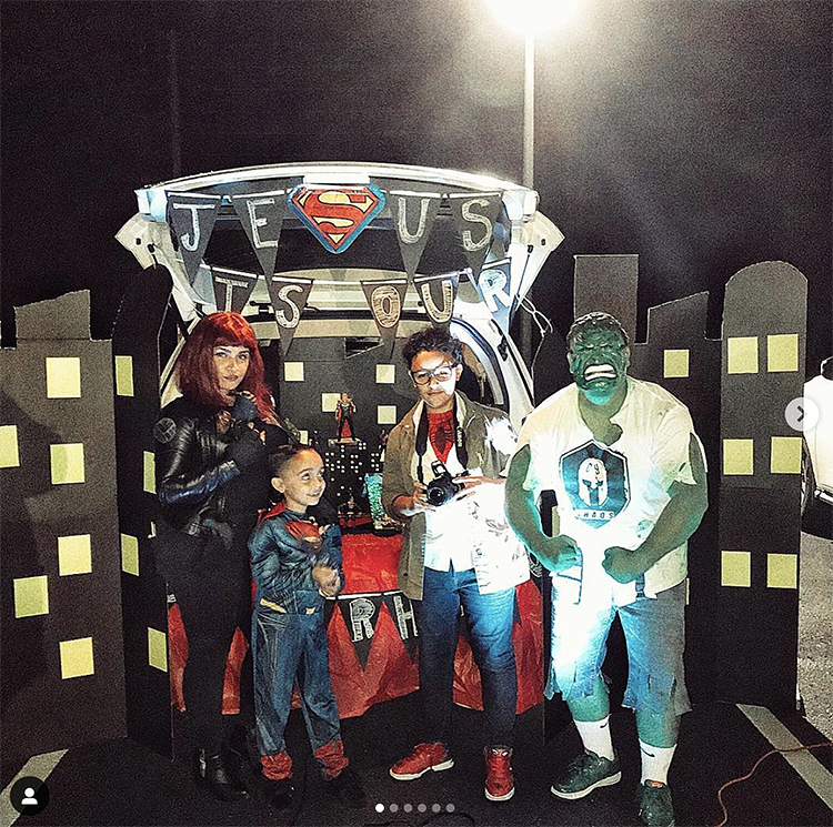 "Trunk decorated as a city from a superhero movie. A sign reads ""Jesus is our Superhero"". The family is dressed as various superhero characters to match the trunk or treat theme. 