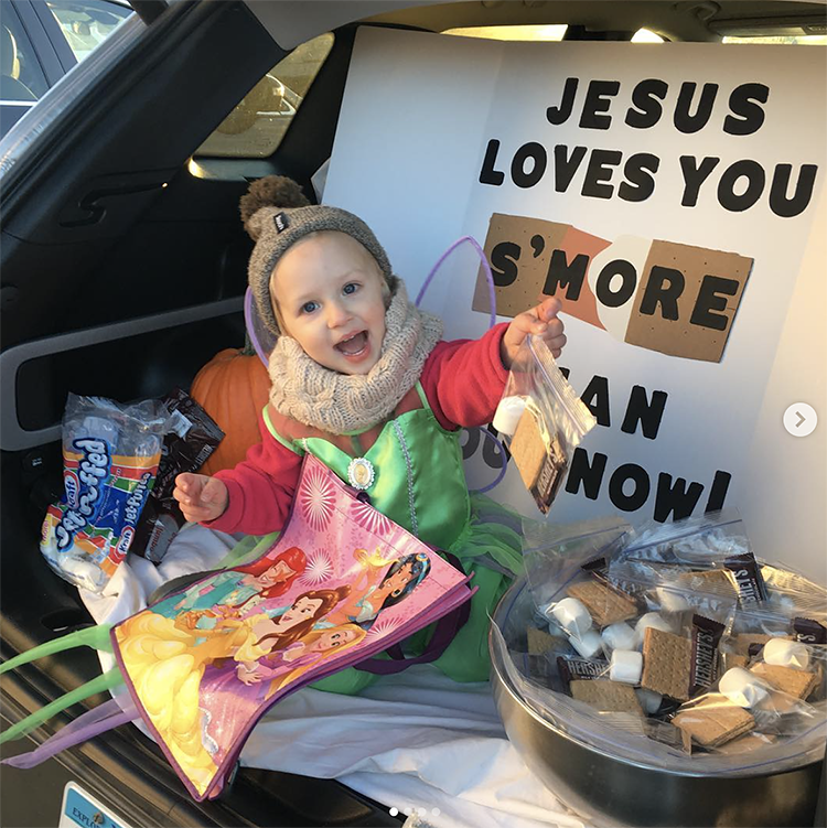 "A trunk decorated with a sign that says ""Jesus loves you s'more than you know"". The treat for the trunk or treat activity is a bag of supplies to make s'mores. 