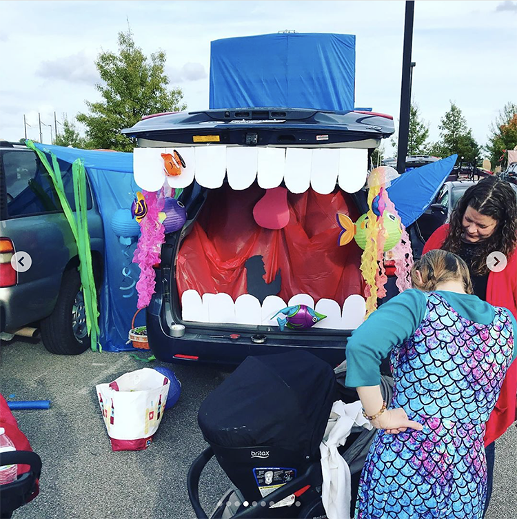 A trunk decorated as a large whale. Inside of the whale is the silhouette of a man praying (Jonah). This is a great trunk or treat theme for church! | The Dating Divas