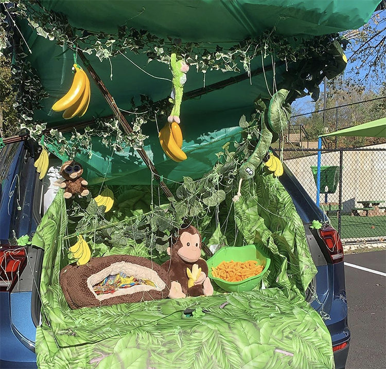 A trunk decorated as a jungle. It includes a lot of greenery, banana and a stuffed monkey. This is a fun trunk or treat theme idea for family animal costumes to do with the theme. |The Dating Divas
