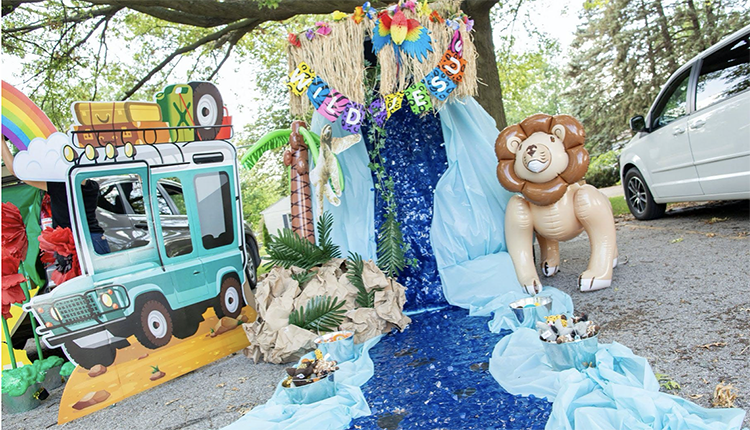 A trunk decorated with a safari jeep cutout and a large waterfall and river made from fabric. An inflatable palm tree and lion add to creating a safari and jungle feel. This is a fun trunk or treat idea for church. | The Dating Divas