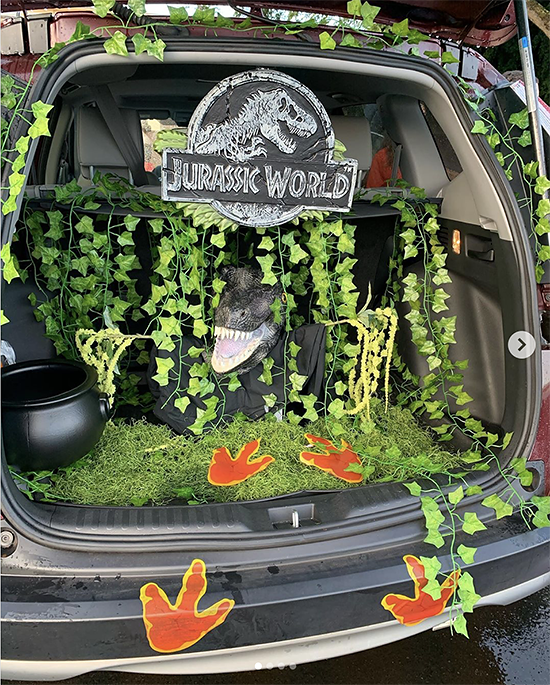 Trunk decorated with a theme for the movie Jurassic Park. It includes a lot of vines and greenery, the park's logo and printed dinosaur footprints leading to the trunk. This is a great trunk or treat idea | The Dating Divas