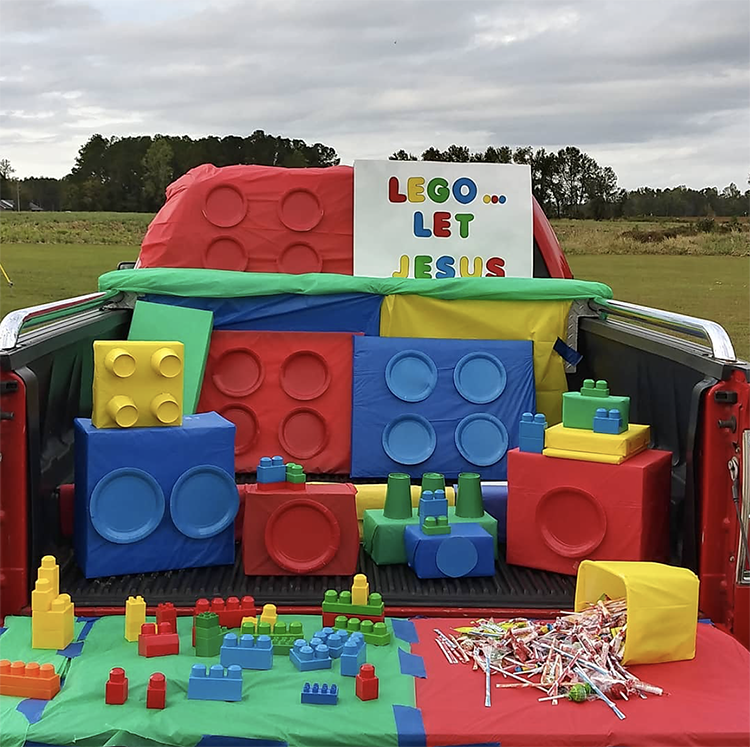 "A trunk decorated with legos. The boxes are wrapped in colorful wrapping paper with matching paper places. A sign reads, ""Lego and let Jesus"" making this an easy trunk or treat idea for a church trunk or treat event. 