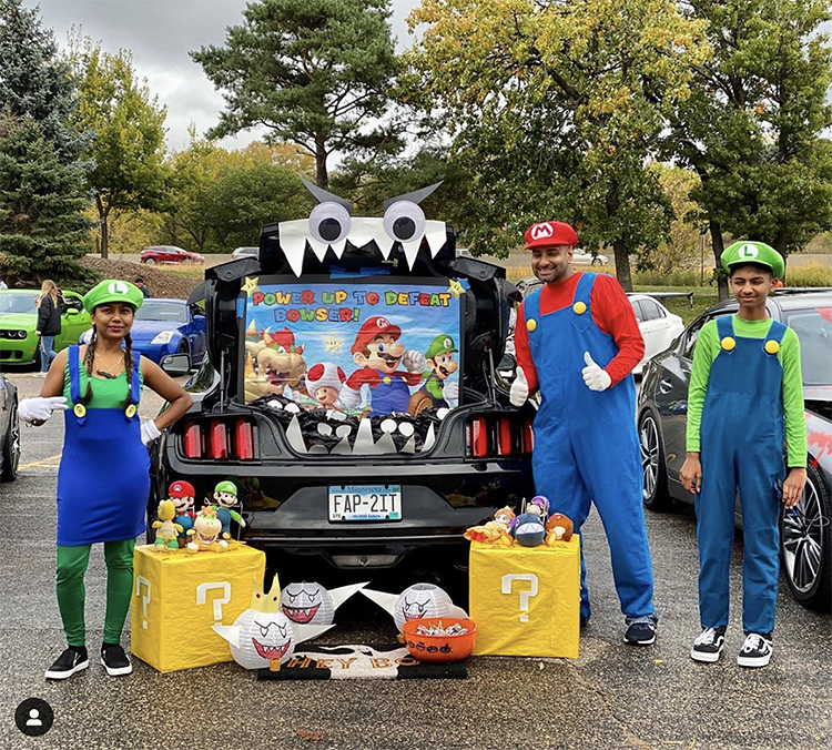 A trunk decorated to the theme of the video game Mario Cart. The family is dressed as characters from Mario cart to match the trunk's Halloween Trunk or Treat theme. | The Dating Divas
