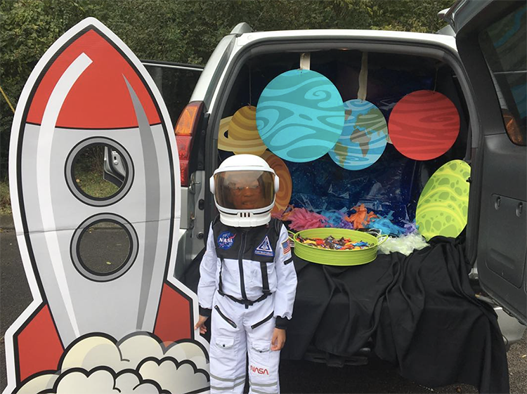 A trunk decorated with planets. The trunk is space with hanging planets and a large rocket ship cut out. A child is dressed as an astronaut to match the car's space trunk or treat theme. | The Dating Divas