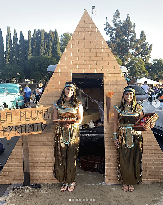 A trunk elaborately decorated with a cardboard replica of the pyramids of Giza. The people giving out candy are dressed as ancient Egyptians. A clever Halloween trunk or treat theme. | The Dating Divas