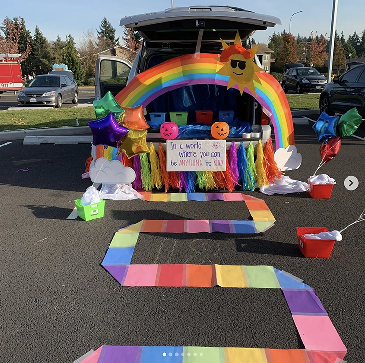 A trunk decorated with the colors of the rainbow. There is a pathway leading two the car which has a large rainbow stretched across the back of the trunk. This is a super popular trunk or treat theme for a Halloween event. | The Dating Divas