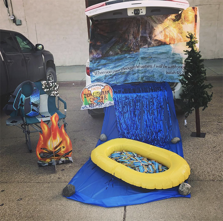 A trunk decorated with a river spilling out of the car. A small raft is placed on the river and filled with candy. A sign includes a quote from Isaiah in the Bible about passing through the waters with the Lord with you. | The Dating Divas
