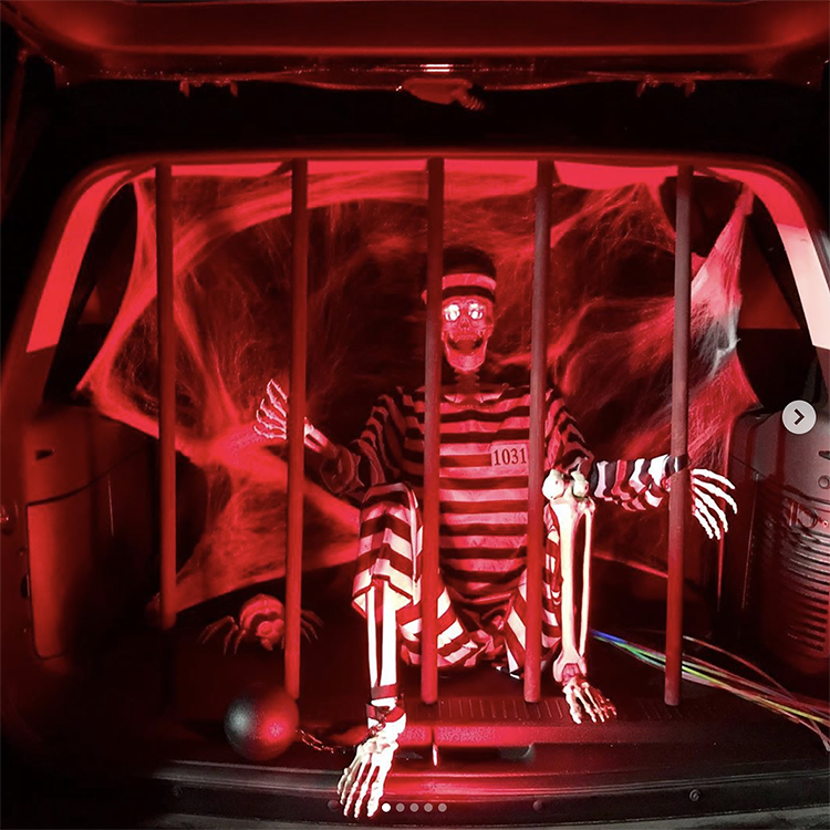 A trunk decorated with red lights lighting a jail cell. Inside the jail is a skeleton. This is a fun idea for a scary trunk or treat theme | The Dating Divas