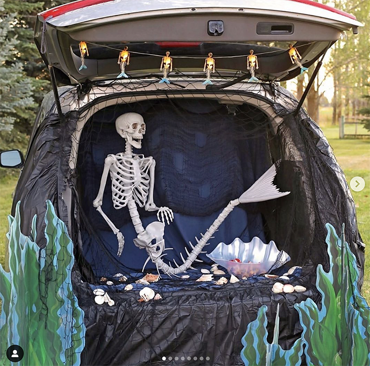 A trunk decorated with an under the sea scene. Inside the trunk is a skeleton mermaid. This is a fun idea for a scary trunk or treat theme | The Dating Divas