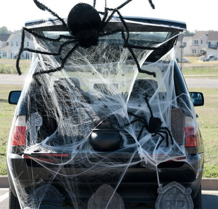 A trunk decorated as a spider web. It has a giant large spider and the trunk is filled with cobwebs. This is an easy trunk or treat idea for decorating your trunk for Halloween. | The Dating Divas