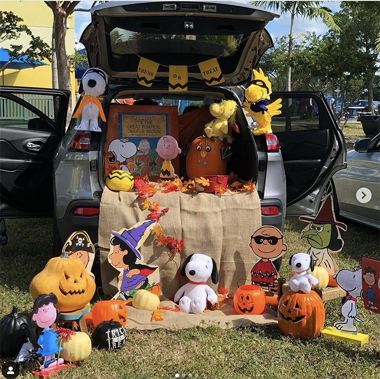 A trunk decorated with the theme of Charlie Brown's Great Pumpkin. There are several Snoopy character cutouts and stuffed animals included Lucy, Charlie Brown and Woodstock. There are also a lot of pumpkins. This is a fun Halloween trunk or treat idea. | The Dating Divas