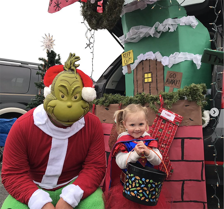 Trunk decorated with a theme for the movie and book The Grinch Who Stole Christmas. It includes scenes from Whoville. A parent and child is seen in a Grinch and Cindy Lou costume to coordinate with the trunk's theme. This is a great trunk or treat idea | The Dating Divas