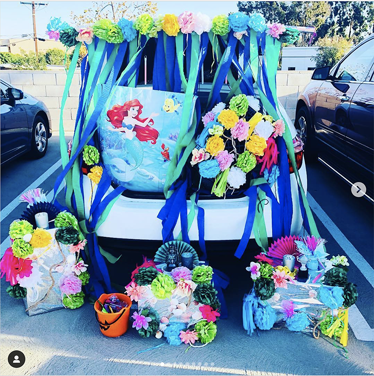 Trunk decorated with a theme for the Disney movie The Little Mermaid. It includes a lot of blue streamers and scenes from the movie. This is a great trunk or treat idea | The Dating Divas