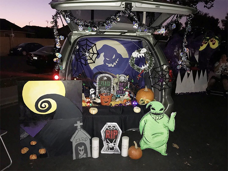Trunk decorated with a theme for the movie The Nightmare Before Christmas. It includes cutouts with scenes and characters from the movie. This is a great trunk or treat idea | The Dating Divas