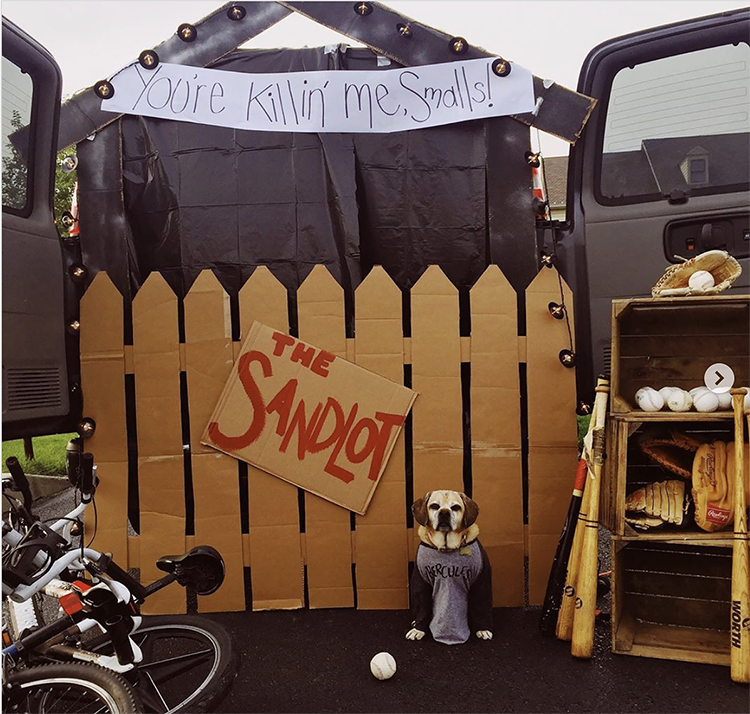 Trunk decorated with a theme for the movie Sandlot. It includes a picket fence, a sign and baseball bats and balls. This is a great trunk or treat idea | The Dating Divas