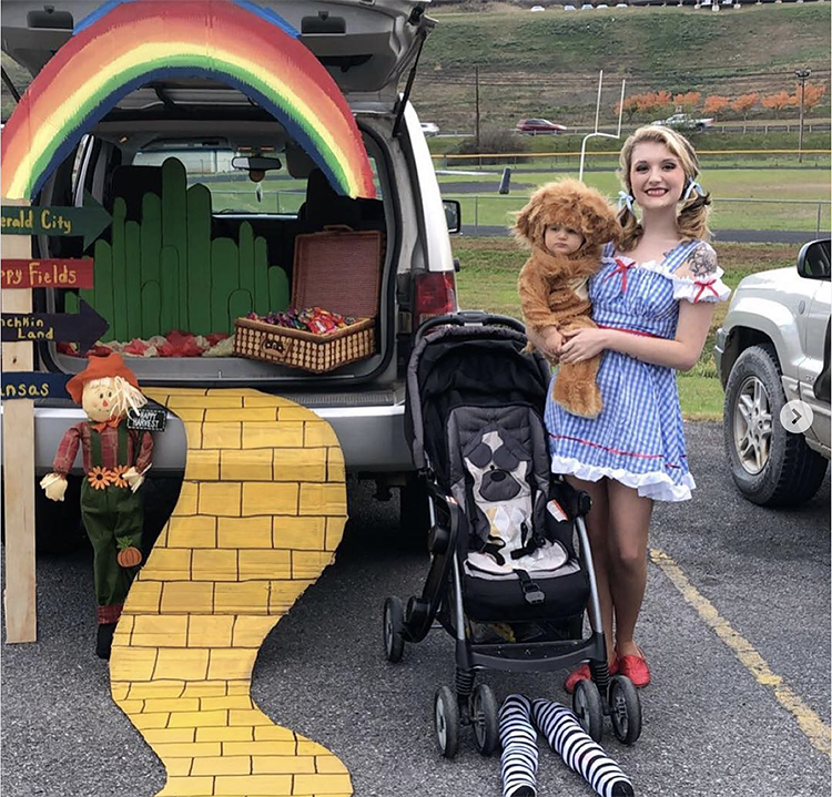 Trunk decorated with a theme for the classic movie The Wizard of Oz. It includes a yellow brick road leading to the car and a large rainbow stretching across the car's trunk. A mother and child are dressed as Dorothy and the Lion - characters from the move. This is a great trunk or treat idea | The Dating Divas