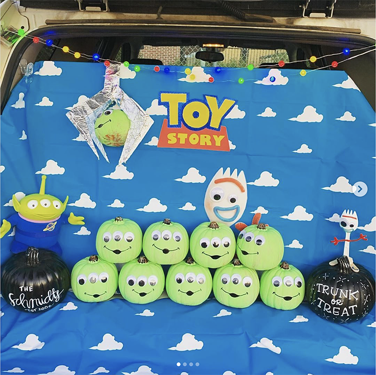 Trunk decorated with a theme for the Disney movie Toy Story. It includes pumpkins decorated as the green aliens from Pizza Planet. This is a great trunk or treat idea | The Dating Divas