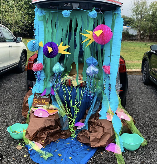 A trunk decorated with an under the sea theme. It includes colorful fish and blue streamers. This is a very colorful trunk or treat decorating idea! | The Dating Divas
