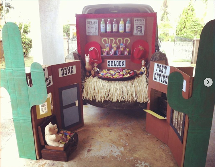 Trunk decorated as a Wild West scene. It includes various buildings including a post office, bank and saloon. There are cacti and wanted posters. This is a great trunk or treat idea for Halloween | The Dating Divas