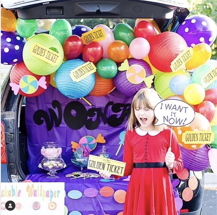 Trunk decorated with a Charlie and the Chocolate Factory theme. It includes a lot of colorful balloons, and some printed golden ticket labels. This is a great trunk or treat idea | The Dating Divas
