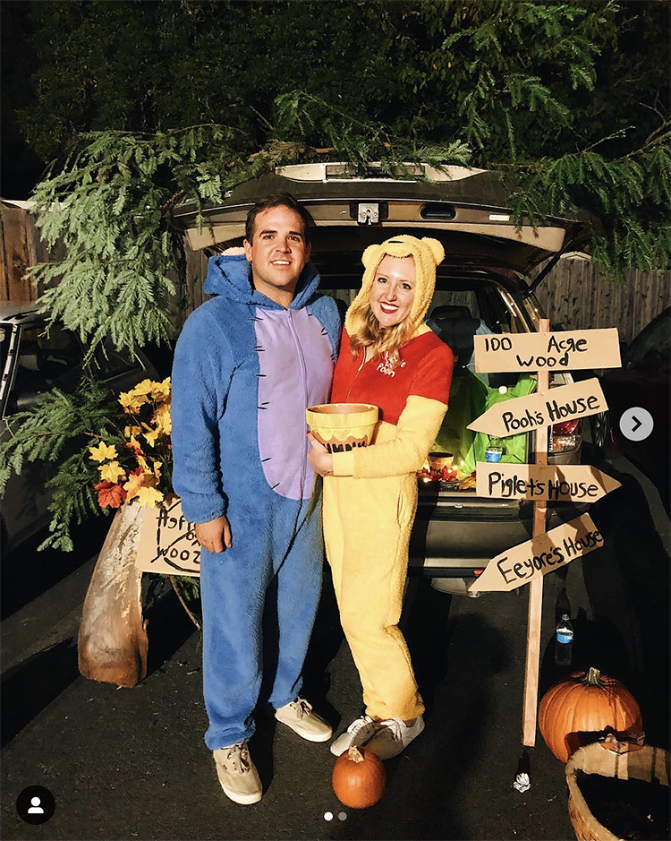 Trunk decorated with a theme for the movie and book Winnie the Pooh. It includes signs for the 100 acre woods. A couple is dressed as Eeyore and Winnie the Pooh to coordinate their costumes with the trunk's theme. This is a great trunk or treat idea | The Dating Divas