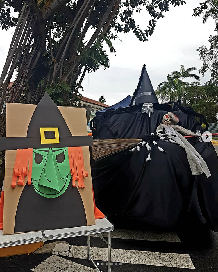 A trunk decorated as a large witch stretching across the bed of a truck. This is a fun idea for a scary trunk or treat theme | The Dating Divas