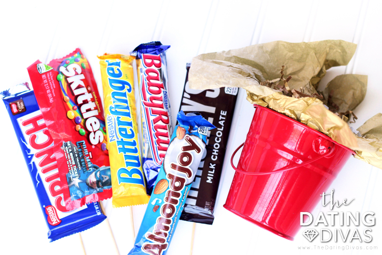 Red bucket and candy bars to build a DIY candy bouquet for that special someone. | The Dating Divas