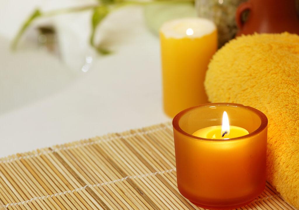 A glowing candle next to a bubble bath showing an example of how to make a DIY spa day at home. | The Dating Divas