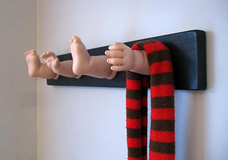Toy doll arms and legs are used as pegs in a coat rack home decoration - also a hilarious gag gift for a Christmas party | The Dating Divas